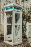 Charming wood telephone booth at a cobblestone alley. Marvao, Portugal - July 10, 2018. Charming painted wood telephone booth at a cobblestone alley, in a sunny stock image