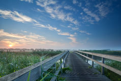 Charming wooden bridge over river at misty sunrise Stock Images