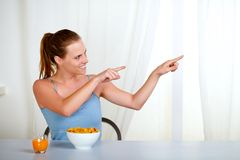 Charming youmg woman eating meal and pointing Stock Images