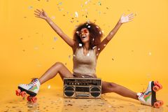 Charming young african woman in retro wear and roller scates throwing confetti while sitting with boombox. Isolated on yellow background stock photo
