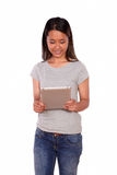 Charming young asiatic woman reading on tablet pc Royalty Free Stock Photos