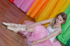 Charming young ballerina puts on Pointe shoes with ribbons royalty free stock images