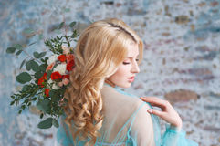 Charming young blond woman holding fresh flowers Royalty Free Stock Images