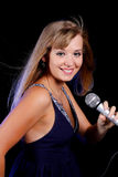 A charming young blonde on a black background with a microphone Royalty Free Stock Images