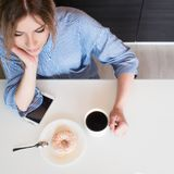 Charming young blonde eat Breakfast at home. Coffee with donut. Top view Royalty Free Stock Images
