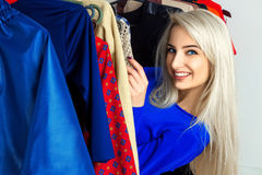Charming young blonde girl smiling in clothing store. Happy young lady with a lot of clothes. Shopping concept Stock Photography