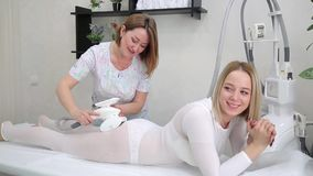Charming young blonde at a massage LPG session. A beautiful girl with big eyes tidies up the figura with a massage in the salon stock video footage