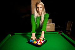 Charming young blonde puts balls in triangle on pool table Stock Images