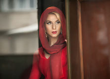 Charming young blonde with red blouse and headscarf posing in door frame. Sensual gorgeous young woman in red outfit Royalty Free Stock Photos