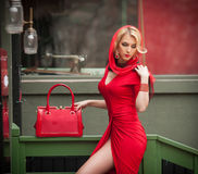 Charming young blonde with red dress, head scarf and bag. Sensual gorgeous young woman in red outfit with Marilyn Monroe look Royalty Free Stock Photo