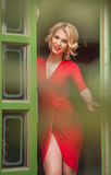 Charming young blonde with red dress posing in a green painted door frame. Sensual gorgeous young woman in red outfit with Marilyn. Monroe look, opening the Royalty Free Stock Image
