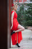 Charming young blonde in red sexy dress with red flower in hair posing against wooden wall.Sensual gorgeous young woman Royalty Free Stock Photos