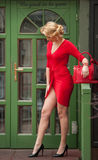 Charming young blonde in red sexy dress posing in front of a green painted door frame. Sensual gorgeous young woman on high heels Royalty Free Stock Photos