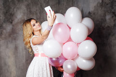 Charming young blonde in a white dress, holding a large bundle of balloons. Happy and cheerful girl makes a selfie. Stock Images
