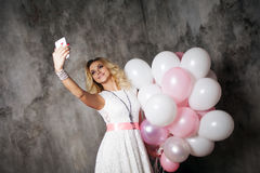 Charming young blonde in a white dress, holding a large bundle of balloons. Happy and cheerful girl makes a selfie. Stock Photo