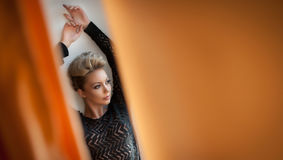 Charming young blonde woman in black blouse posing provocatively, photo through orange curtains. Sexy gorgeous young woman Royalty Free Stock Photos