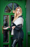 Charming young blonde woman with white fur posing in a green painted door frame. Sexy gorgeous young woman with long curly hair Royalty Free Stock Photo