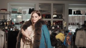 Lovely girls posing in a winter coat. Charming young blondie finds and puts on a luxury blue coat indoor. She is posing in front of mirror in it stock footage