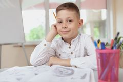 Charming young boy sketching in his textbook royalty free stock image