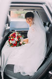 Charming young bride with her bridal bouquet in wedding car limousine Royalty Free Stock Photo