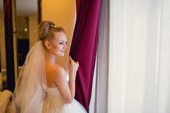 Charming young bride looking out the window and smiling Stock Photos