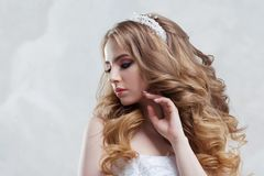 Charming young bride with luxury hairstyle. Beautiful woman in wedding dress. Hairstyle with fluffy curls. royalty free stock photo