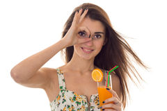 Charming young brunette girl in summer clothes with floral pattern shoing OK and drinks orange cocktail isolated on Royalty Free Stock Photo