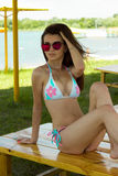 Charming young brunette girl in swimsuit and sunglasses looking away. On a bench Royalty Free Stock Image