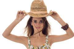 Charming young brunette girl wiht straw hat and summer clothes with floral pattern looking at the camera isolated on Royalty Free Stock Photo