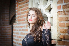 Charming young brunette woman in black lace blouse near a red brick wall. Sexy gorgeous young woman with long curly hair Royalty Free Stock Image