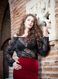 Charming young brunette woman in black lace blouse, red skirt and high heels near the brick wall. Sexy gorgeous young woman Stock Photography