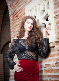 Charming young brunette woman in black lace blouse, red skirt and high heels near the brick wall. Sexy gorgeous young woman Royalty Free Stock Photo