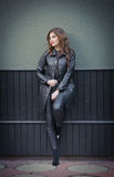 Charming young brunette woman in black leather outfit, coat and trousers, with dark gray wall on background. Sexy gorgeous woman Stock Photos