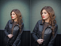 Charming young brunette woman in black leather outfit, coat and trousers, with dark gray wall on background. Sexy gorgeous woman Royalty Free Stock Photos