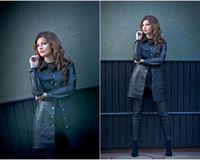 Charming young brunette woman in black leather outfit, coat and trousers, with dark gray wall on background. gorgeous woman Royalty Free Stock Photos