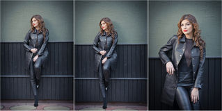 Charming young brunette woman in black leather outfit, coat and trousers, with dark gray wall on background. Sexy gorgeous woman Stock Photography