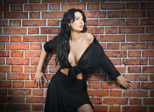 Charming young brunette woman in black near the brick wall. Sexy gorgeous young woman with low cut blouse. Portrait of a provocative woman with long hair Stock Photos