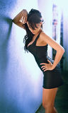 Charming young brunette woman in black tight fit dress posing against a wall Royalty Free Stock Image
