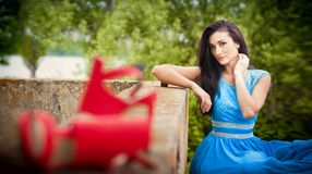Charming Young Brunette Woman In Bright Blue Dress With Red Shoes In Foreground. Sexy Gorgeous Fashionable Woman, Outdoor Shot