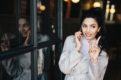 Charming young brunette woman with pleasant smile having gentle. Hands and beautiful manicure communicating over mobile phone with her friend raising her finger stock images