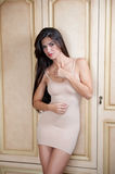 Charming young brunette woman in tight fit short nude dress leaning against wooden wall. gorgeous long hair girl Royalty Free Stock Images