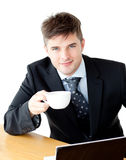 Charming young businessman holding a cup smiling Stock Photos