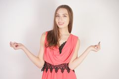 A charming young caucasian girl in an evening dress stands without makeup and holds an open pink lipstick on a white background in. The Studio isolated stock images