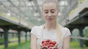 Charming young Caucasian woman holding strawberry in hands and looking at camera. Portrait of beautiful female biologist