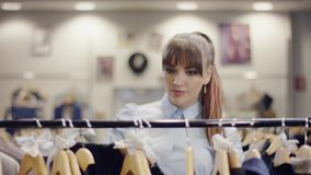 Charming young woman looking for a perfect shirt on a rack of clothes in a clothing store. Charming young caucasian woman looking for a perfect shirt on a rack stock footage