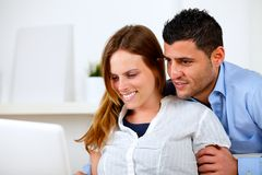 Charming young couple browsing Internet on laptop Stock Photos