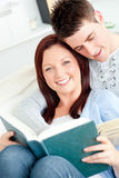 Charming young couple reading a book on the sofa Royalty Free Stock Image