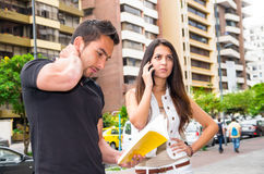 Charming young couple standing outside in urban environment, holding open book and woman talking on mobile interacting Stock Photo