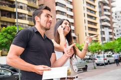 Charming young couple standing outside in urban environment, holding open book and woman talking on mobile interacting Royalty Free Stock Photo