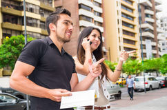 Charming young couple standing outside in urban environment, holding open book and woman talking on mobile interacting Royalty Free Stock Images